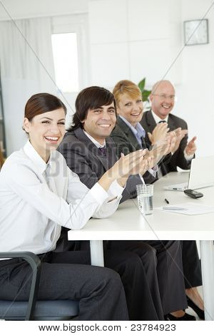 closeup of group of business people applauding at a meeting