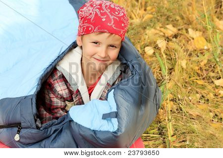 Cute little boy in sleeping bag outdoor.