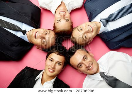 Five businesspeople lying in circle, looking at camera and smiling