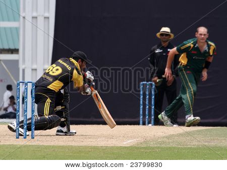 PUCHONG, MALAYSIA - SEPT 24: Malaysia's Hammad Khan (69) bats Guernsey's Jamie Nussbaumer's bowl in this Pepsi ICC WCL Div 6 finals at the Kinrara Oval on September 24, 2011 in Puchong, Malaysia.