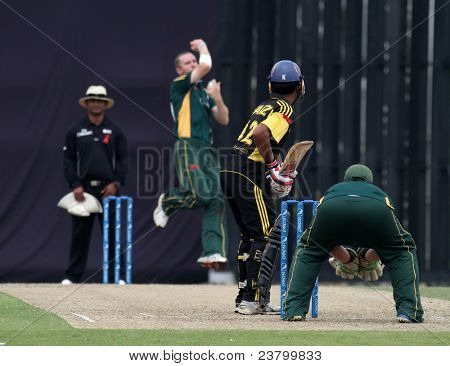 PUCHONG, MALAYSIA - SEPT 24: Malaysia's Ahmad Faiz (12) bats Guernsey's Jeremy Frith's bowl in this Pepsi ICC WCL Div 6 finals at the Kinrara Oval on September 24, 2011 in Puchong, Malaysia.