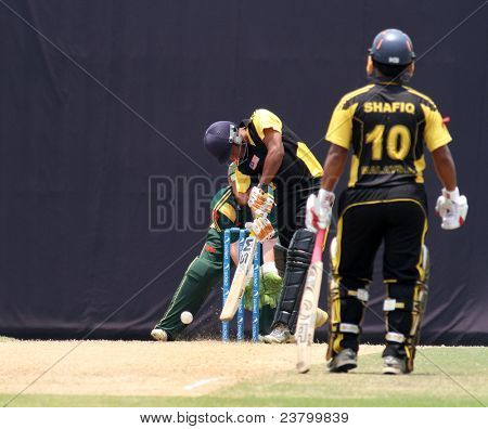 PUCHONG, MALAYSIA - SEPT 24: Malaysia's batsman Hammad Khan bats as M. Shafiq (10) watches in this Pepsi ICC WCL Div 6 finals vs Guernsey at the Kinrara Oval on September 24, 2011 in Puchong, Malaysia