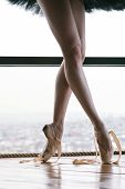 Slender ballerina feet in pointe shoes. She is standing on tiptoe by the window in a black ballet tutu. Pointe shoes are not tied.