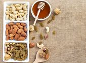 Dried fruits and variety of nuts in a dish with honey in a bowl on the wooden table, such as figs, almonds, raisins, cashews, and pistachio. with copy space for your text.