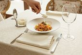 Waiter is adding grated cheese to pasta in expensive restaurant