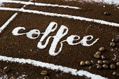 The word coffee is written on ground coffee next to coffee beans. Coffee Industry poster