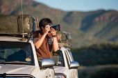 Young Asian Man Traveler And Photographer Sitting On The Car Window Photographing Sunrise During Roa poster
