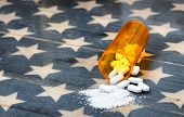 Front View Of Prescription Bottle Filled With Generic Opioid Pain Killer Tablets On Rustic Usa Flag  poster