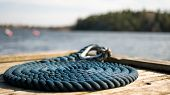Coastal Dock On A Rocky Area With Blue Nautical Sailing Rope For Boats And Yachts. poster