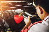 Car Mechanic Replacing With Pouring  Oil Into Engine poster