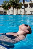 High Angle View Of Beautiful Girl In Sunglasses And Swimwear Resting In Swimming Pool. poster