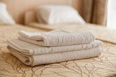 Stack Of White Hotel Towel On Bed In Hotel. Soft Focus. poster
