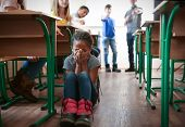 Bullied African American girl sitting on floor in classroom poster