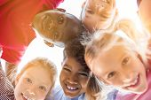 Portrait of happy kids in circle looking down and embracing. Group of five multiethnic friends outdo poster