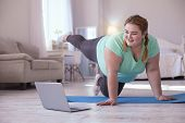 Video Lesson. Obese Young Woman Repeating Exercises While Watching Online Workout Session poster
