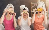 Three Beautiful Girls In Colourful Clothes And With Towels On Heads Having Fun, Covering Eyes With L poster
