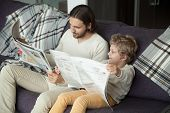 Cute Kid Son Holding Newspaper Sitting On Sofa With Dad, Curious Funny Clever Boy Pretending Reading poster