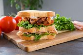 Fresh Triple Decker Turkey Club Deli Sandwich On Cutting Board poster