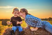 Mom Kisses Her Son At Sunset. Mom And Son Are Sitting On A Haystack In The Field At Sunset. Rural Li poster