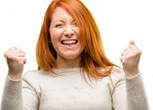 Beautiful young redhead woman happy and excited expressing winning gesture. Successful and celebrati poster
