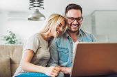 Joyful Couple Relax And Work On Laptop Computer At Modern Living Room Indoor Home poster