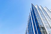 Detail Of Office Building Exterior. Business Buildings Skyline Looking Up With Blue Sky. Modern Arch poster