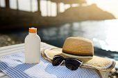 Suntan Cream Bottle And Sunglasses On Beach Towel With Sea Shore On Background. Sunscreen On Deck Ch poster