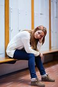 foto of snob  - Portrait of a sad student sitting on a bench looking at the camera - JPG