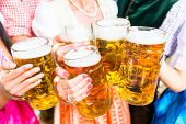 Clinking glasses with beer in Bavarian beer garden, close-up on five beer glasses poster