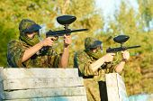 picture of paintball  - Two paintball sport players in prootective uniform and mask aiming and shoting with gun outdoors - JPG