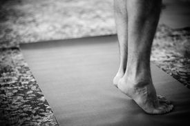 picture of yoga mat  - Male feet standing on the yoga mat - JPG