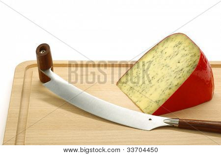 piece of traditional frisian cheese with herbs and a cheese cutter on a wooden cutting board on a white background
