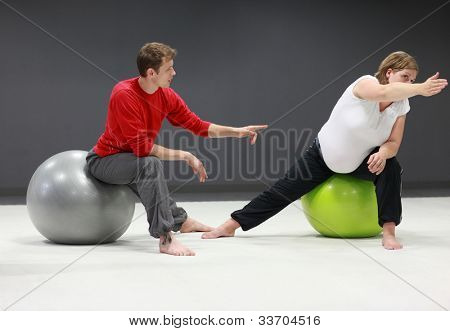 Physical therapist massaging pregnant woman's arm