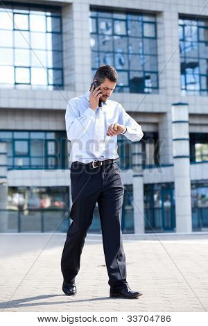businessman on  phone and checking his watch in front of his office building, running late