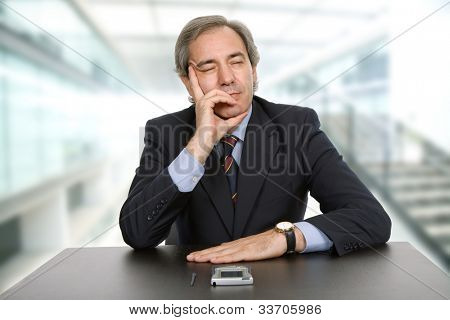 mature business man on a desk, sleeping, at the office