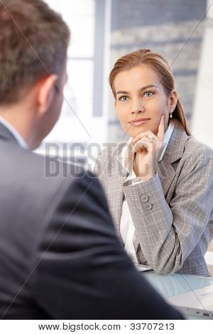 Beautiful businesswoman interviewing male applicant in bright office, smiling.