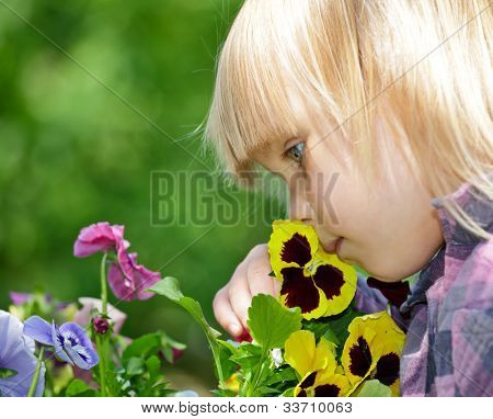Little girl smelling flowers in a garden