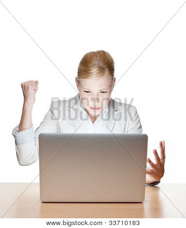 Young business woman sitting at a office desk with laptop, isolated