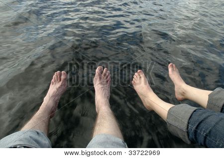 feet dangling over water