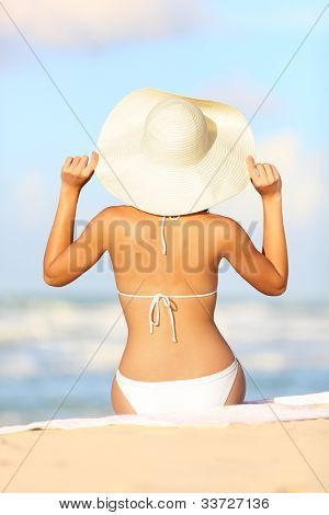 Travel vacation woman on summer holiday on beach holding her summer hat sitting in the sand enjoying ocean. Back view of beautiful girl in white bikini.