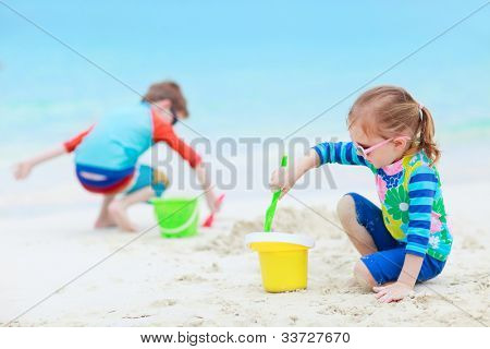 Brother and sister together on tropical beach playing with toys