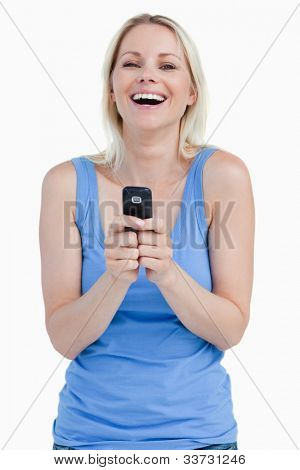 Laughing woman sending a text with her cellphone against a white background
