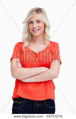 Smiling fair-haired teenager crossing her arms against a colourless background