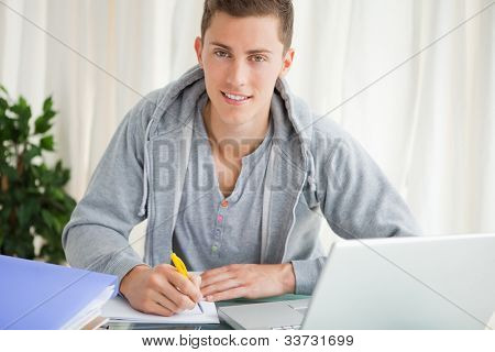 Portrait of a student doing his homework with a laptop on his desk