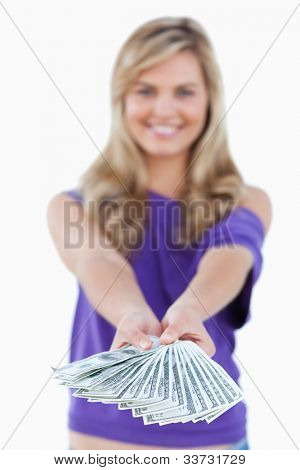 Fan of bank notes being held by a blonde woman against a white background