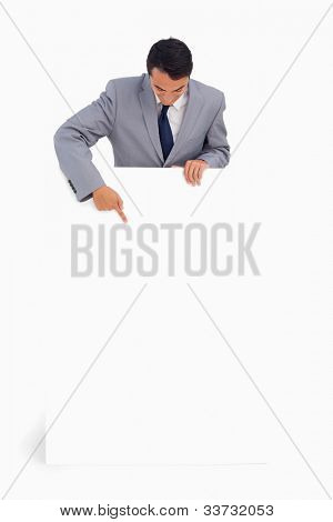 Good-looking man behind a big poster against white background