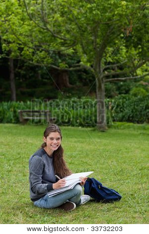 Smiling teenage girl doing her homework while sitting on the grass in the countryside