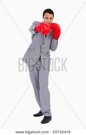 Businessman wearing red boxing gloves against white background