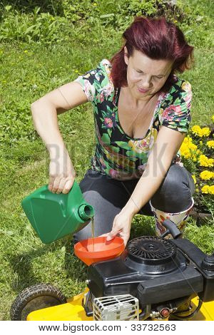 Women adding oil to lawn mover
