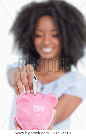 Pink piggy bank getting dollar notes while being held by a young attractive woman